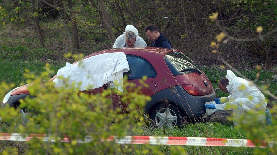 Männer in weißen Overalls untersuchen einen roten Ford Ka - Weißes Tuch deckt den Vorderbereich ab