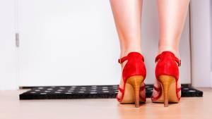 Eine junge Frau steht vor einem Fußabstreifer