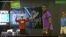 Tennisspieler Frances Tiafoe steht beim eigenen Aufschlag mit dem Ball in der Hand und muss lachen.