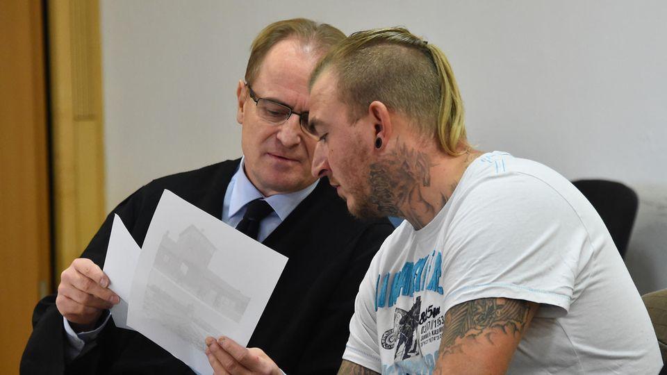 NPD-Politiker Marcel Zech (r.) bespricht sich mit seinem Anwalt im Gerichtssaal in Neuruppin