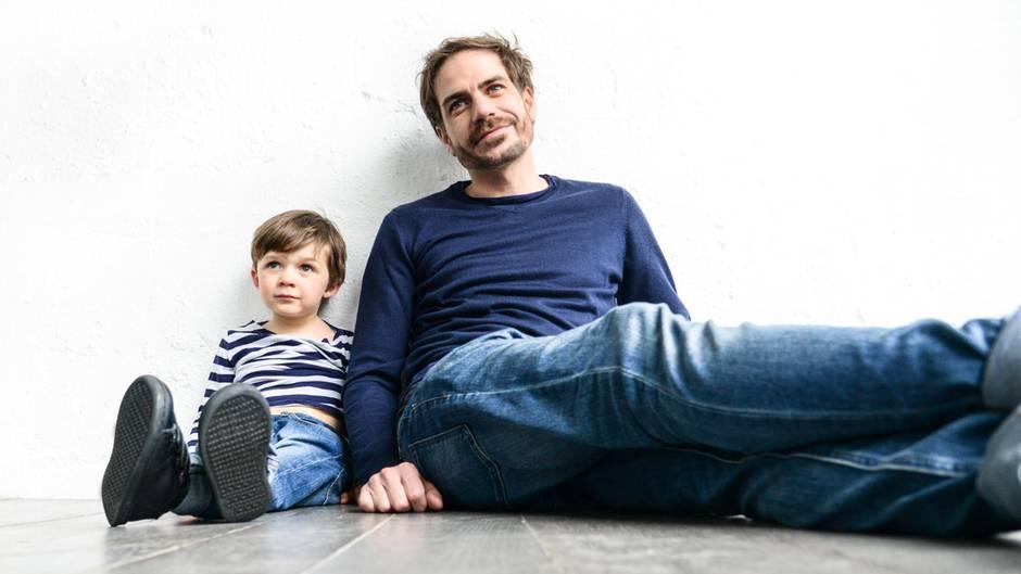 Vater und Sohn sitzen auf dem Boden, an eine Wand angelehnt