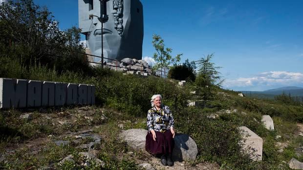 """Die Gulag-Überlebende Stefanija vor der """"Maske der Trauer"""" in Magadan, sitzend, vor einer grünen, abschüssigen Landschaft"""