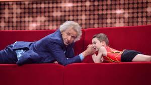 Thomas Gottschalk liegt im blauen Anzug auf einem roten Sofa und macht Armdrücken mit einem kleinen Jungen in Ringer-Dress