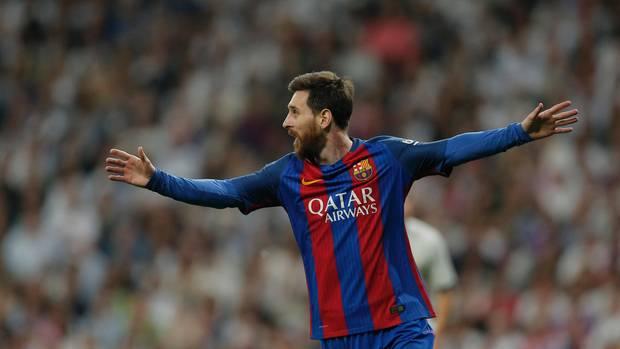 Lionel Messi läuft im rot-blau gestreiften Trikot des FC Barcelona mit ausgebreiteten Armen jubelnd über den Rasen