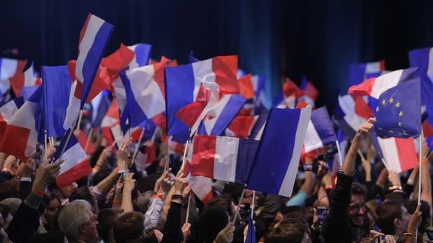 Anhänger des französischen Präsidentschaftskandidaten Emmanuel Macron schwenken französische Flaggen