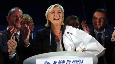 Marine Le Pen steht bei der Präsidentschaftswahl mit einem Strauß Blumen im Arm lächelnd hinter einem Rednerpult