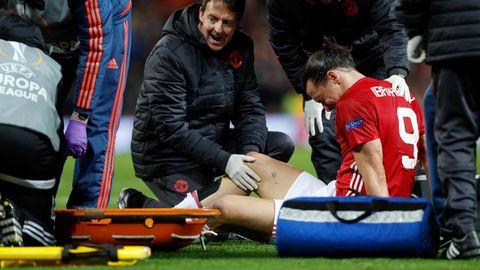 Zlatan Ibrahimovic sitzt mit schmerzverzerrtem Gesicht auf dem Rasen, während ein Betreuer sein rechtes Knie untersucht.