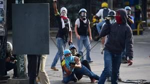 Drei vermummte junge Männer in Venezuela spannen eine Schleuder, um etwas auf Polizisten zu schießen