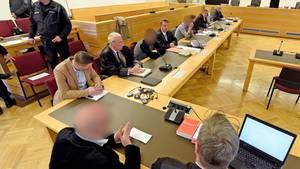 Die Angeklagten mit ihren Verteidigern beim Prozessauftakt in Hannover. Polizisten sichern den Gerichtssaal und das Gebäude.