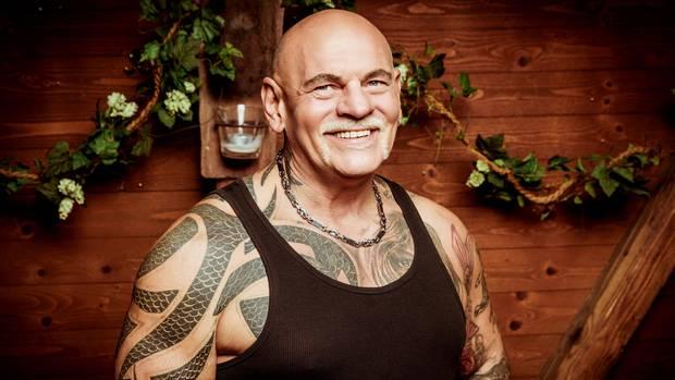 Alfred, ein kräftiger Mann mit Glatze und Tattoos unter dem schwarzen Unterhemd, lächelt vor einer Holzwand in die Kamera