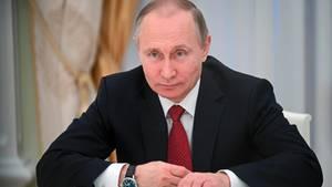 Russlands Präsident Wladimir Putin sitzt auf seine Unterarme gestützt im dunklen Anzug am Schreibtisch