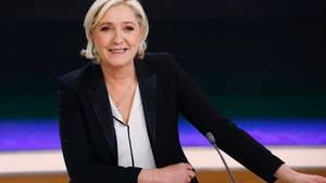 Marine Le Pen sitzt in einem Fernsehstudio vor einer blauschwarzen Wand und lächel