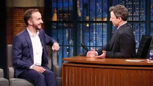Jan Böhmermann sitzt links auf einem Sessel, während Moderator Seth Meyers hinter seinem hölzernen Schreibtisch sitzt