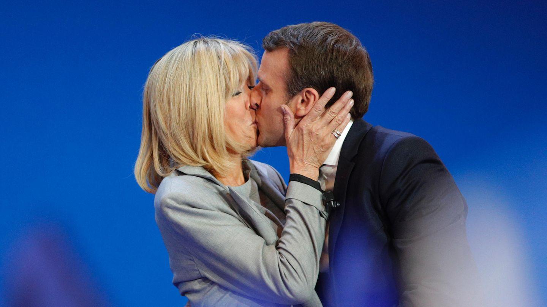 Emmanuel Macron und seine Frau Brigitte küssen sich nach seinem Wahlerfolg auf einer Bühne vor blauem Hintergrund