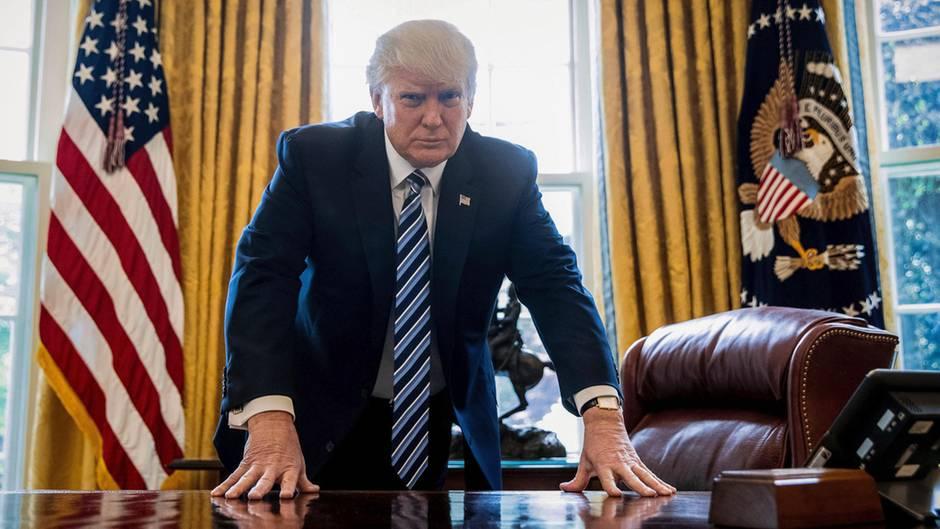 Donald Trump stützt sich auf den Schreibtisch des Oval Office im Weißen Haus