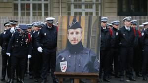 Ein Porträt des Pariser Polizisten Xavier Jugele steht bei der Trauerfeier für den bei einem Terroranschlag Erschossenen.