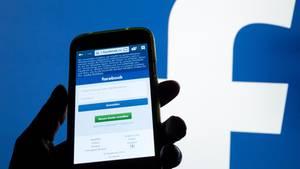 Ein Smartphone Display mit der Login-Seite von Facebook leuchtet vor einer Wand mit einem großen Facebook-Logo