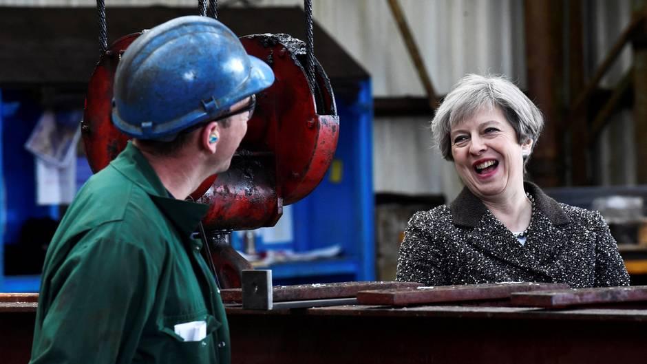 Die britische Premierministerin Theresa May plaudert während ihres Besuches in einem Stahlwerk mit einem Arbeiter.