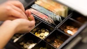 Eine Kassiererin zählt Geld in einer Supermarktkasse