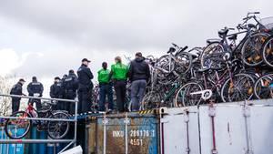 Beamte der Polizei in Hamburg stehen vor meterhoch aufgetürmten Fahrrädern, bei denen es sich vermutlich um Diebesgut handelt.