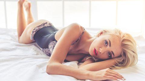 Eine sexy Frau räkelt sich auf dem Bett