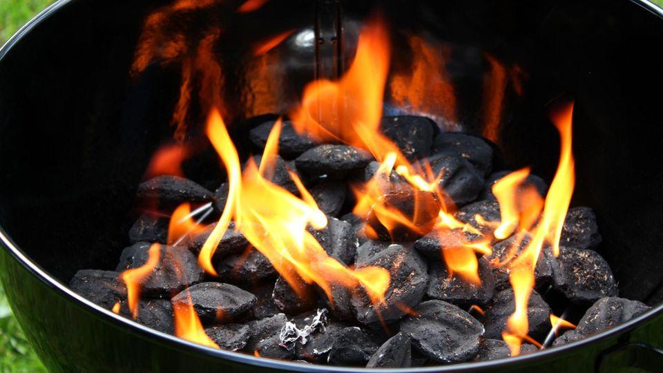 Flammen schlagen zwischen der Holzkohle in einem Kugelgrill