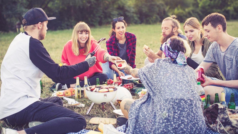 Junge Menschen sitzen auf einer Wiese und grillen zusammen
