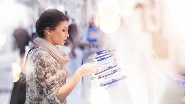 Eine Frau schaut sich im Laden Smartphones an
