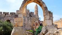 Jerusalem, Israel. Zugegeben, er ist gut versteckt. Aber irgendwo auf diesem Foto befindet sich der berühmte Davidsturm von Jerusalem. Sehen Sie's? Wir verraten es Ihnen: Er befindet sich hinter dem schlecht angemalten nackten Mann, unter dem Steinbogen.