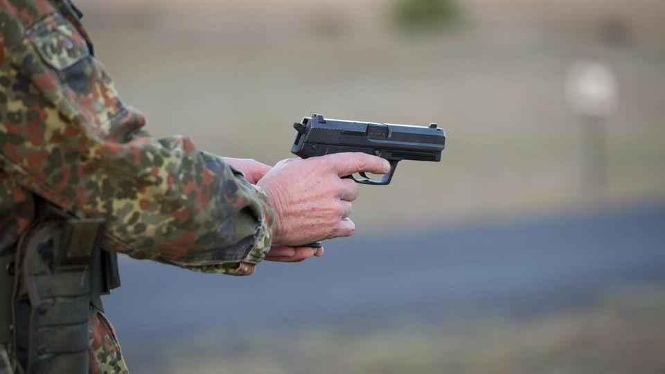 Ein Bundeswehrsoldat in Tarnfleck-Uniform hält mit beiden Händen eine Pistole