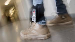 Am linken Bein eines Mannes ist über einer Jeans eine elektronische Fußfessel zu sehen