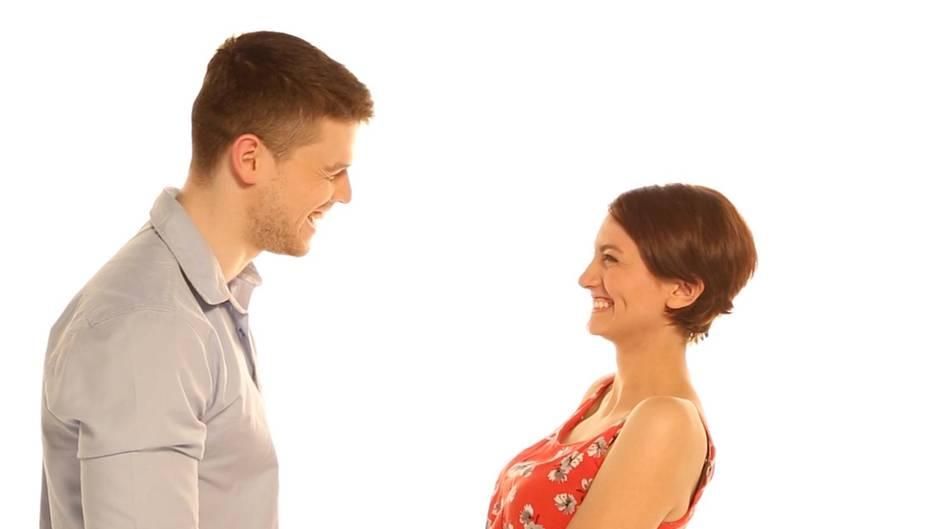 Ein Mann in Hemd und eine Frau im Sommerkleid stehen sich gegenüber und lachen sich an