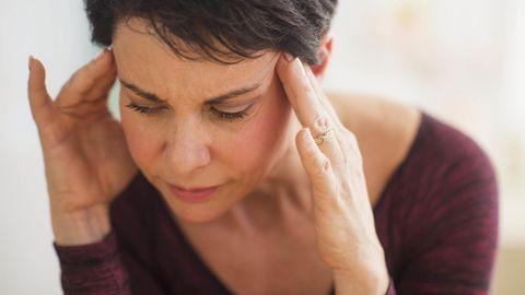Eine Frau hat Kopfschmerzen und hält sich den Kopf.