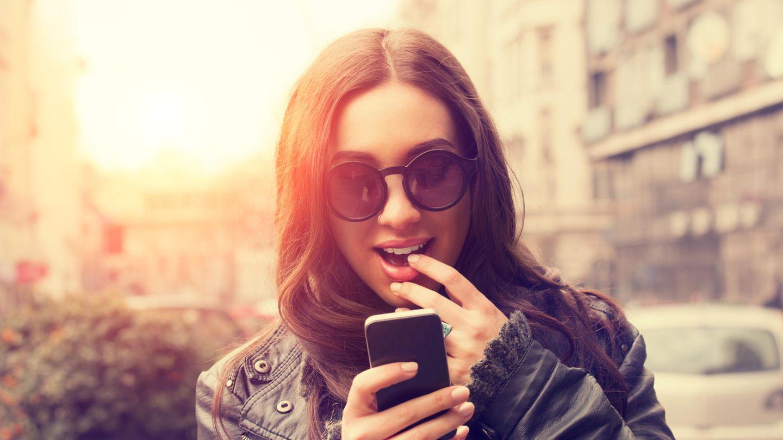 Eine junge Frau betrachtet aufgeregt ihr Smartphone