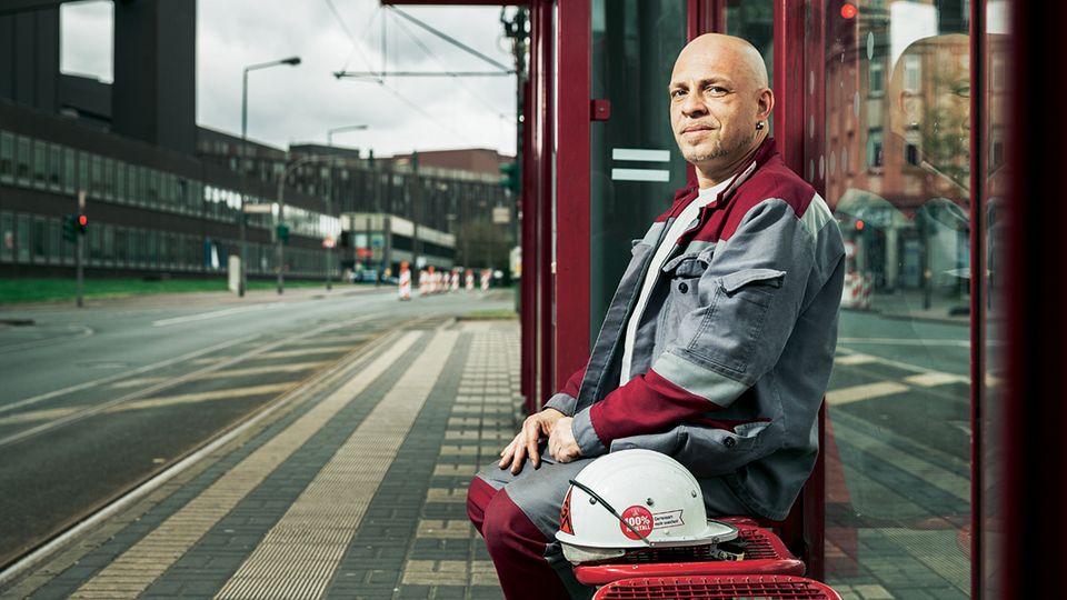 An der Haltestelle Thyssen Verwaltung wartet Patrick Weber, der sich Sorgen um seinen Job im Stahlwerk macht