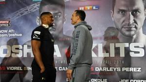 Anthony Joshua und Wladimir Klitschko stehen sich auf der Pressekonferenz gegenüber und müssen lachen.
