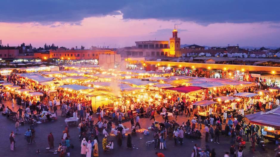 """Marrakesch in Marokko:Verwinkelte Gassen, duftende Tajine, bunte Basare und blühende Gärten  Wenn wir, wie Ray Bradbury behauptete, wegen der Romantik, der Architektur und aus dem Wunsch heraus reisen, uns zu verirren, dann ist Marrakesch ein Volltreffer. Die legendäre """"Rote Stadt"""" besteht aus Mauern aus Lehm und Sandstein, die abends erstrahlen, als wären sie mit der untergehenden Sonne verkabelt. Im Herzen der Anlage liegt die Medina, die Altstadt, die sich im Lauf eines Jahrtausends zu einem riesigen Labyrinth ausgewachsen hat, das geradezu danach schreit, gemeinsam erkundet zu werden."""
