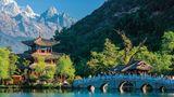 """Provinz Yunnan in China:Geschwungene Brücken, uralte Klöster und tibetische Gebetsfahnen  Romantisch veranlagten Reisenden in die Provinz Yunnan soll gesagt sein, dass es sich bei der auf den Landkarten verzeichneten Region """"Shangri-La"""" im äußersten Südwesten Chinas keineswegs um eine Fiktion handelt. Eigentlich trägt die Region einen anderen Namen, aber als sich alle Welt in das mythische """"Shangri-La"""" verliebte – jenes utopistische Idyll aus dem Roman """"Der verlorene Horizont"""", irgendwo im Himalaya, behaupteten einige Gemeinden, das echte Shangri-La zu sein, und baten Peking um eine Namensänderung. Warum diese Ehre schließlich diesem hinreißenden Landstrich in Yunnan verliehen wurde, versteht man auf der Stelle, wenn sich vor einem die Silhouette des Himalaya erhebt."""