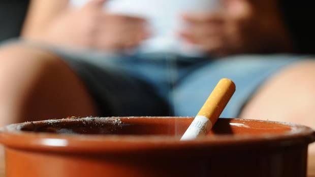 Eine schwangere Frau raucht.