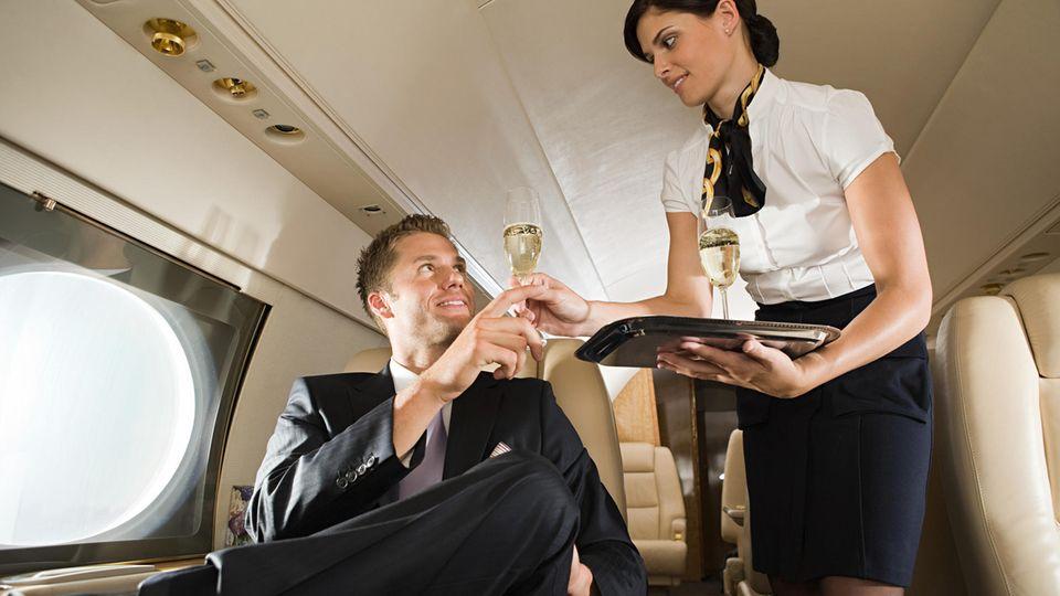 Eine hübsche Stewardess serviert einem Fluggast ein Glas Sekt