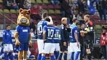 Nach dem Abpfiff steht das abgestiegene Team des Karlsruher SC geschockt auf dem Platz