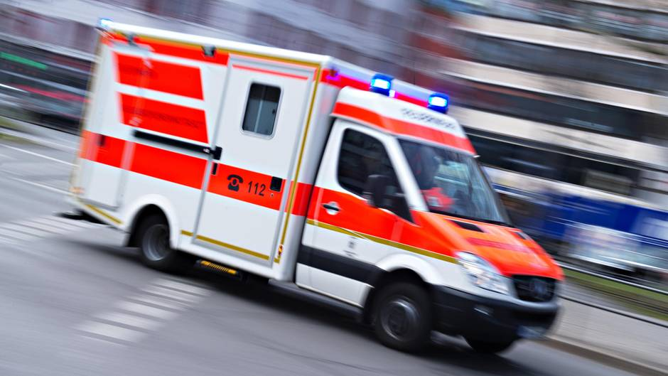 Ein Rettungswagen rast mit Blaulicht durch eine Straße in einer Großstadt