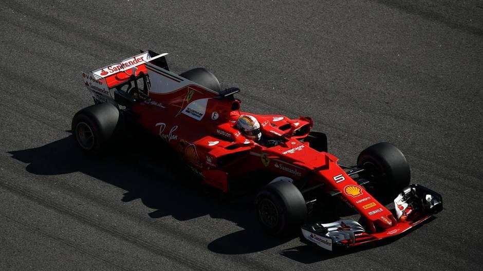 Der rote Ferrari von Sebstian Vettel rast über den dunkelgrauen Asphalt der Formel 1 Rennstrecke in Sotschi
