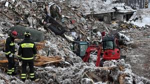 Zwei Feuerwehrmänner und ein Bagger stehen auf den Trümmern des von einer Lawine verschütteten Hotels Rigopiano in den Abruzzen