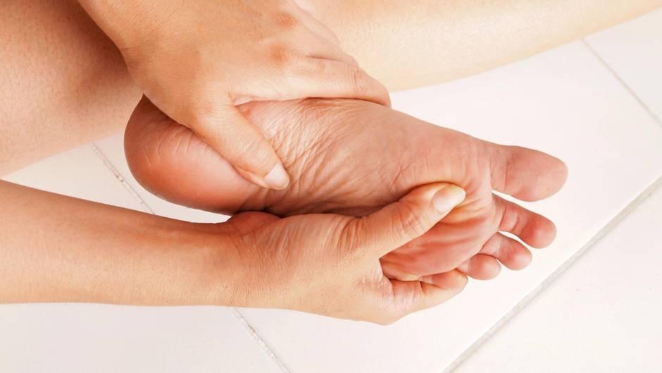 Eine Frau fasst sich an den schmerzenden Fuß.