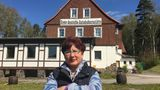 Über einen Zaun hinweg verkauft Christina Wagner ihre Bratwürste an der Autobahnraststätte