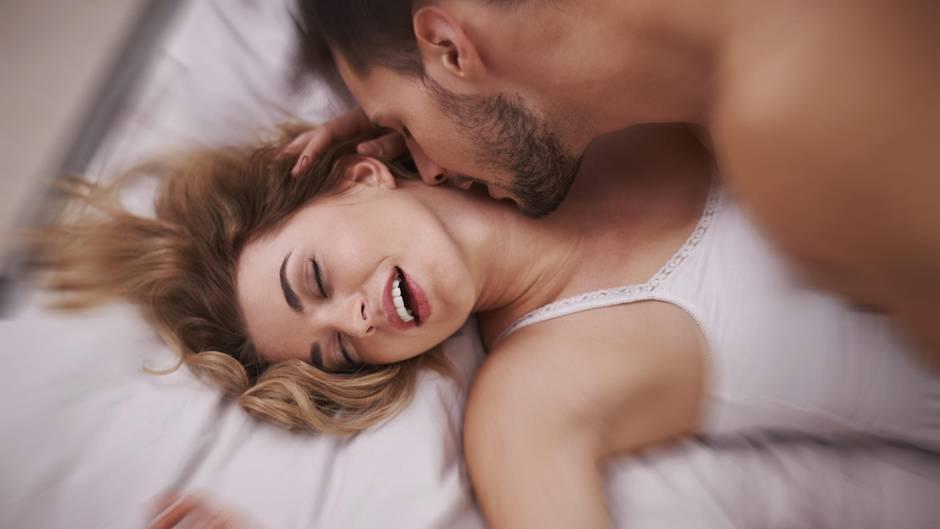 Mann küsst den Hals einer Frau im Bett