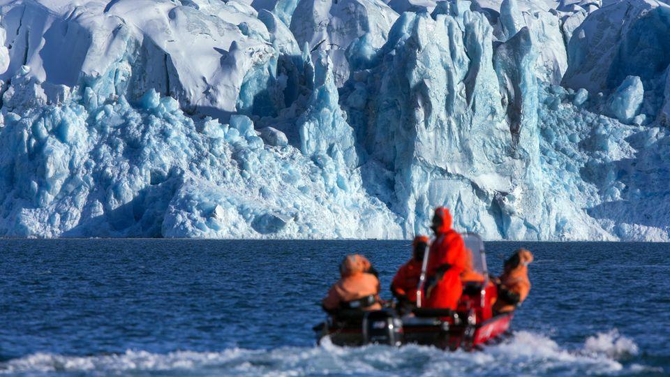 Wissenschaftler fahren in einem Boot zur Kongsfjord-Gletscherfront in der Nähe der Forschungsstation Kings Bay auf Spitzbergen.