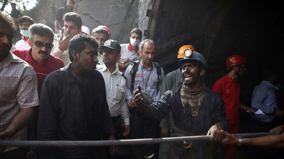 Iranische Bergarbeiter hoffen am Eingang des Bergwerks auf die Bergung der verschütteten Kumpel