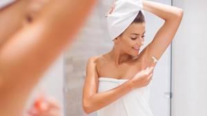 Eine Frau rasiert sich die Achseln